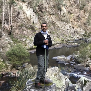 Bachelor of Arts Archaeology student Colin Ahoy on a rock beside a local river