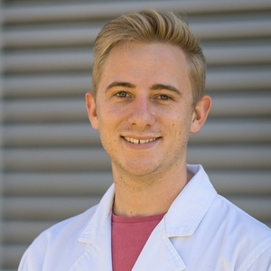 UNE Bachelor of Science (Honours) graduate and PhD student Matthew Hilliar smiles in white lab coat