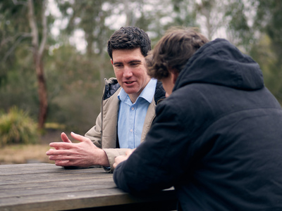 UNE student on park bench discusses studies with a peer